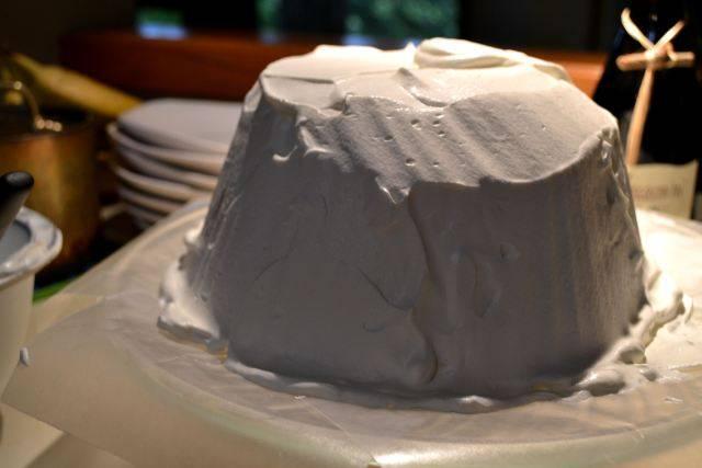 14. Фольгу аккуратно удалить. Взбить оставшиеся сливки до плотных пиков и обмазать им тортик. Украсить сверху какао, измельченными в пудру орешками или тертым шоколадом.