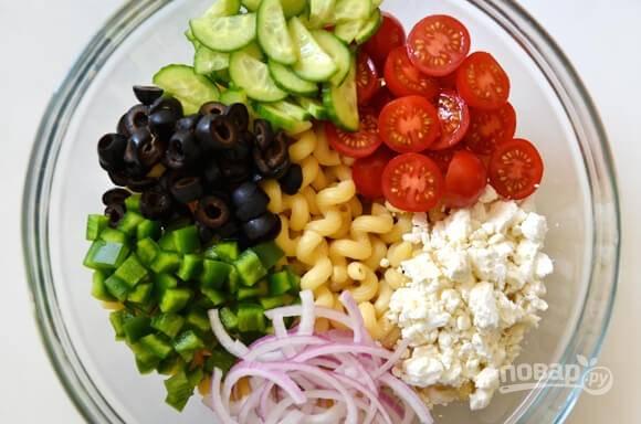 Помидорки режем напополам, огурцы — тонкими полукругами, пере — кусочками, лук — полукольцами. Измельчаем маслины и сыр. Отправляем все с макаронами в миску.