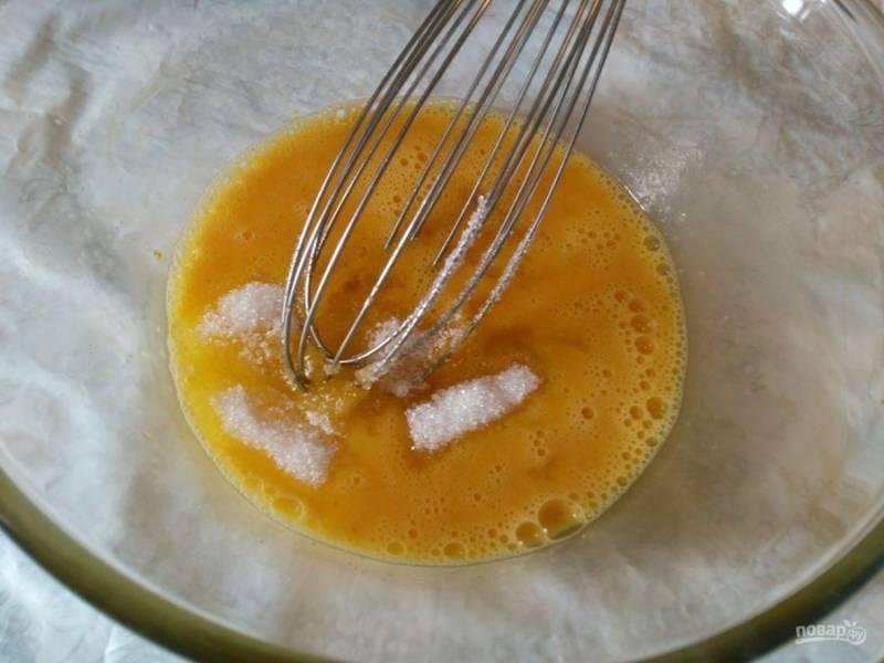 Яйца разбейте в глубокую миску, всыпьте щепотку соли, ванильный сахар и сахарный песок, а затем слегка взбейте венчиком до растворения сахара.