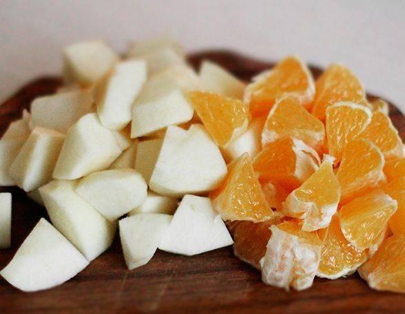 Очищаем яблоко и апельсин и нарезаем небольшими кусочками.