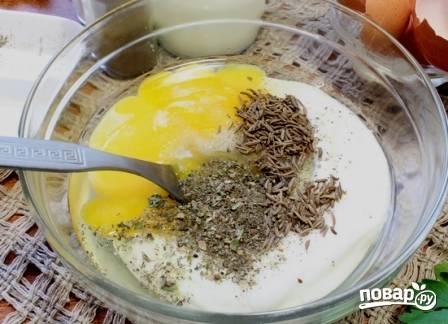Готовим начинку. Вбиваем в миску яйца, добавляем сметану, сухие травы, перец и тмин. Перемешиваем-взбиваем вилкой.