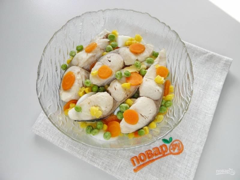И теперь самое приятное: начинаем делать заливное. На дно тарелочки налейте пару столовых ложек бульона. Уложите порезанные морковь, рыбу без костей (внутренние кости можно вытащить пинцетом, чтобы не повредить кусочки), горошек, кукурузу и колечки вареного яйца.