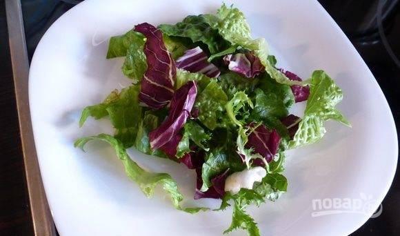 Листья салата вымойте и обсушите. Порвите их руками и выложите на тарелку для подачи. Прекрасно смотрятся разные сорта салата в одной тарелке.