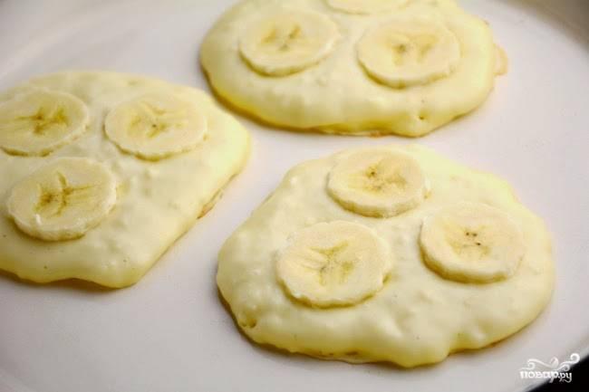 Начинаем выпекать оладьи на растительном масле. Выливаем одну столовую ложку теста, вдавливаем пару кусочков банана.
