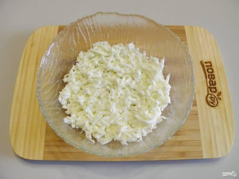 Отделите желтки от белков. Они понадобятся для разных слоев салата. Первым выкладывайте белковый слой, белки же предварительно натрите на крупной терке.