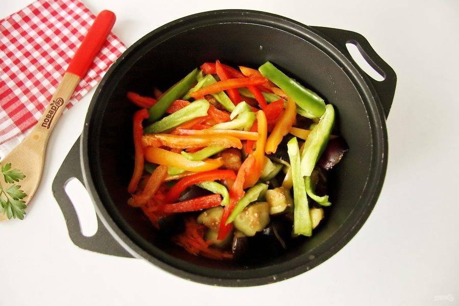 Доведите массу до кипения и проварите, помешивая пару минут. Добавьте промытые и отжатые от влаги баклажаны, нарезанный перец и тертую морковь.