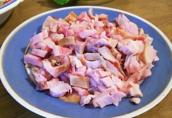С копченой курицы снимаем кожицу и нарезаем мясо на небольшие кусочки.