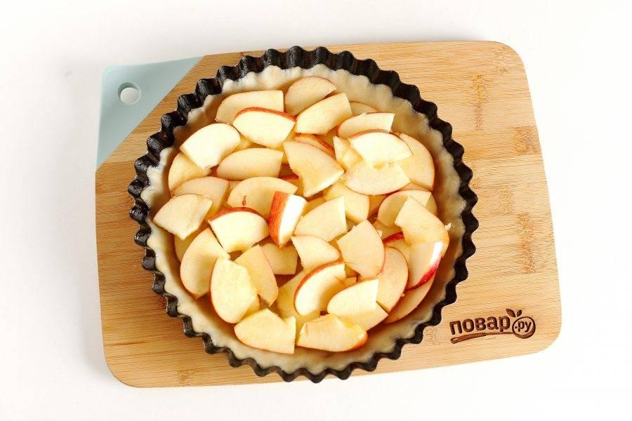 Яблоки вымойте, обсушите и нарежьте. Удалите из них косточки и снимите кожуру. Выложите яблоки в форму для запекания. Если яблоки не сильно сладкие, то дополнительно можно их посыпать сахаром.