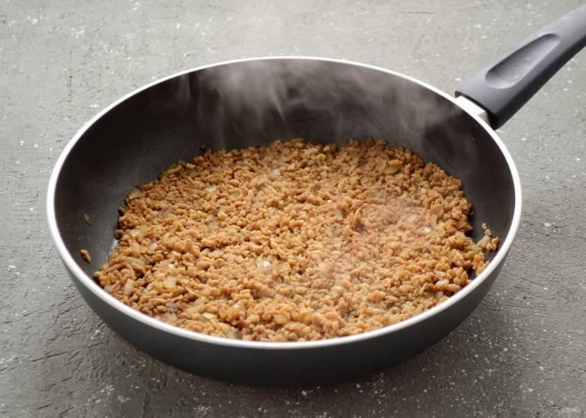 Затем добавьте соевый соус и мисо пасту, хорошо все перемешайте. Налейте в сковороду столько воды, чтобы соевый фарш полностью намок. Продолжайте обжаривать, пока не испарится лишняя жидкость.