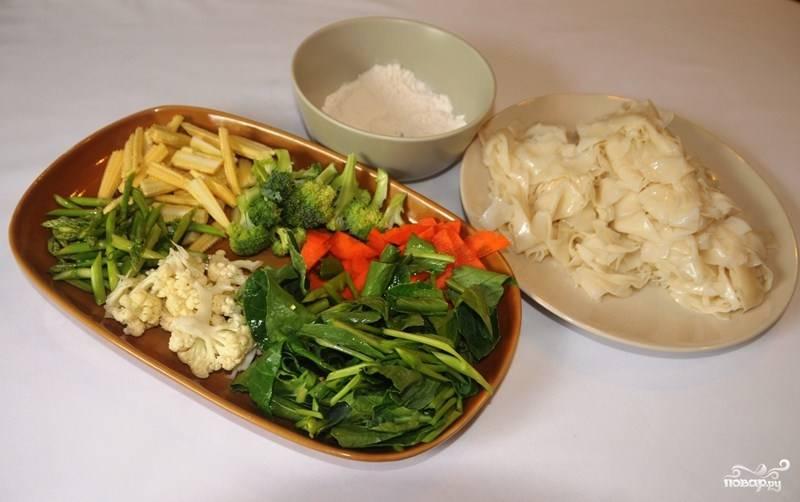 Подготовьте ингредиенты. Рисовую лапшу замочите в холодной воде на несколько минут, чтобы она стала мягкой. Если полоски лапши слишком широкие, можете их порезать ножом или кухонными ножницами на более тонкие полоски.