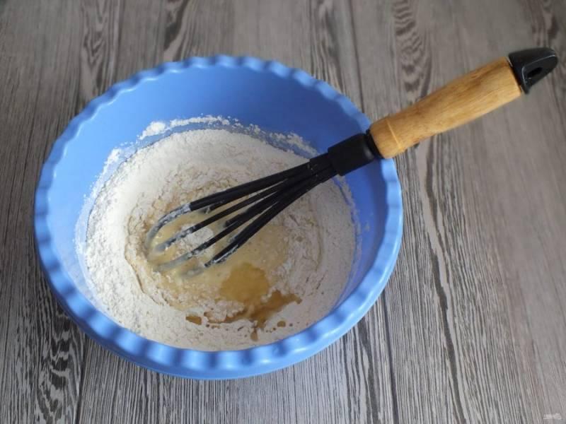Добавьте часть муки и растительное масло. Начните замешивать сначала венчиком, как только станет масса густеть, подсыпьте еще часть муки и продолжите замес руками.