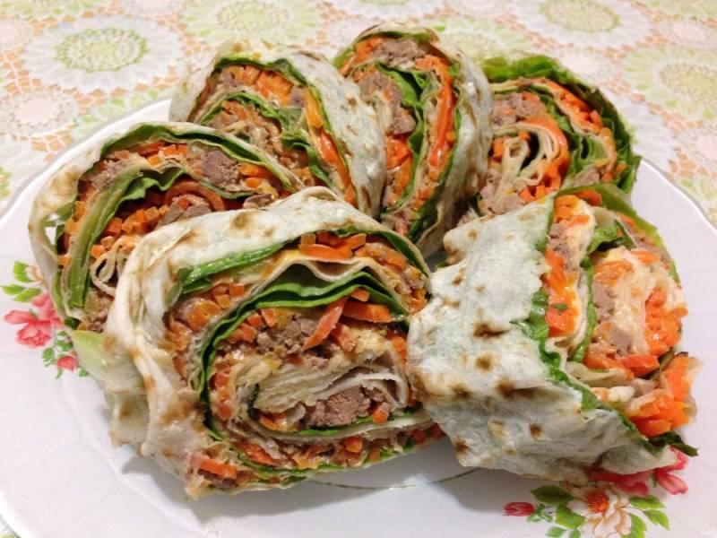 Готовый рулет из лаваша и корейской морковки порежьте на небольшие рулетики и подавайте к столу. Приятного аппетита!