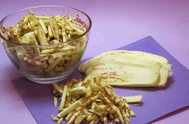 Для начала мы промываем баклажаны под холодной водой, удаляем у них плодоножку и срезаем кожуру, затем нарезаем их брусками.