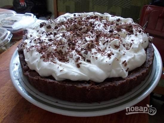 Перекладываем пирог на блюдо, сверху наносим слой взбитых сливок и посыпаем натертым шоколадом. Можно наслаждаться!