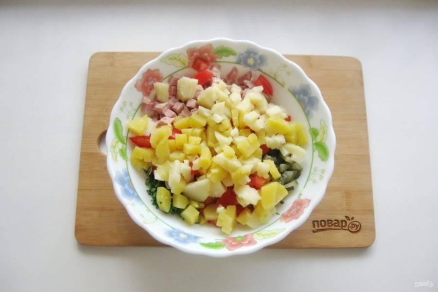 Картофель сварите, охладите и нарежьте кубиками. Добавьте в салат.
