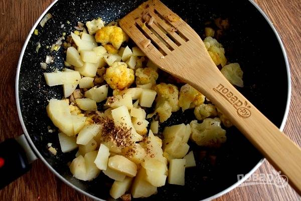 Добавьте картофель, куркуму, кориандр, соль и готовьте под закрытой крышкой в течение двух минут.