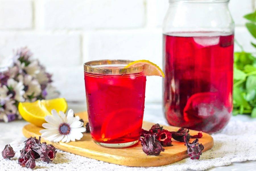 Подайте лимонад из каркаде охлажденным, разлив в стаканы, чашки или в коктейльные банки. По желанию украсьте емкости ломтиками лимона или свежей мятой.