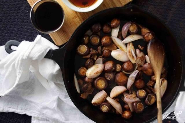 Предварительно отмоченные белые грибы, шампиньоны и очищенный лук-шалот целиком обжарьте на сковороде. Это займет около 8 минут. После этого влейте вино, прокипятите его с луком и грибами в течении минуты, постоянно помешивая. Верните в сковороду утку, залейте водой, оставшейся от отмоченных грибов, и бульоном. Мясо, грибы и лук должны быть полностью покрыты. Добавьте веточки тимьяна.