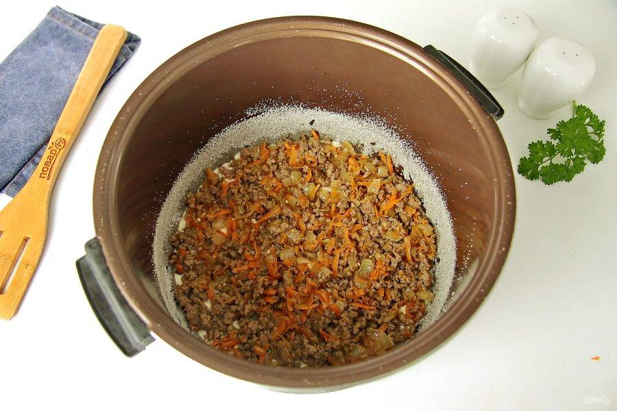 Чашу мультиварки смажьте маслом и обсыпьте дно и бока манкой или мукой. Низ чаши можно застелить пергаментом. Вылейте примерно половину порции теста и разложите на него равномерно начинку.
