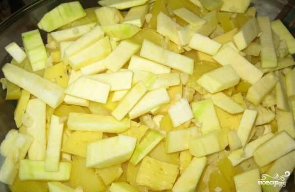 Картофель также вымойте и положите в кастрюльку по размеру. Залейте водой и отварите картофель до полной готовности. Когда он остынет, очистите клубни от кожуры и нарежьте такими же кусочками, как кабачок. Смажьте растительным маслом форму для запекания, выложите в нее нарезанные овощи слоями.
