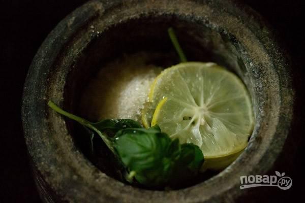 В ступу уложите листья базилика, сахар, лимон и щепотку соли. Разомните ингредиенты.