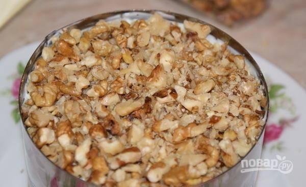 Следующим слоем выложите измельчённые орехи. Немного смажьте их майонезом.