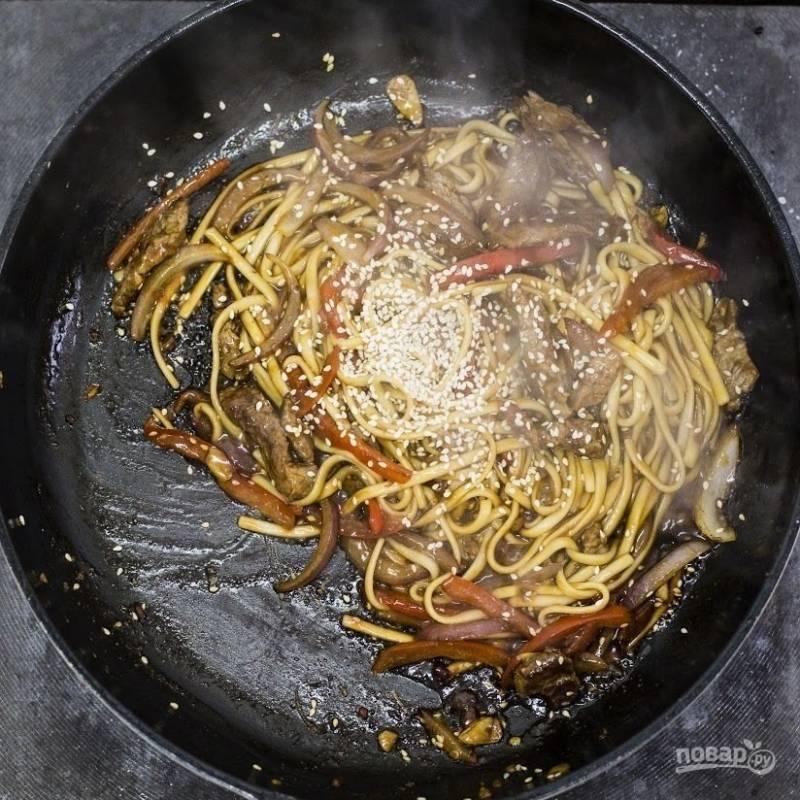 Далее в сковороду добавьте соус, лапшу и кунжут. Перемешайте и тушите блюдо 2 минуты.