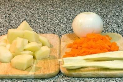 2. Нарежьте овощи крупно - картошку, луковицу, корень петрушки разрежьте на несколько частей, когда уха сварится, его надо будет просто выбрать. Морковь нарежьте полукольцами.