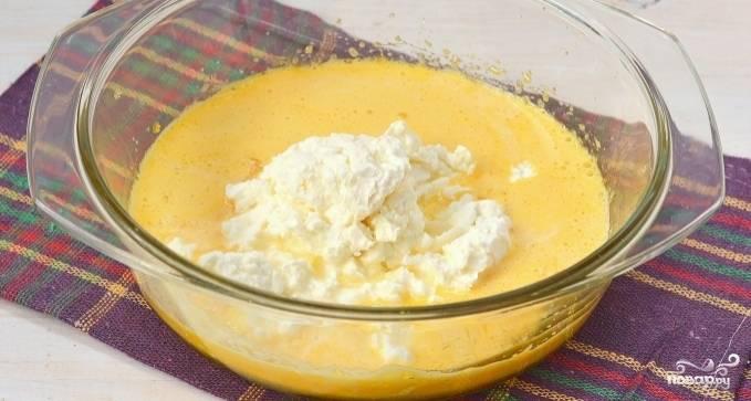 В микроволновке или же на паровой бане растопите кусочек сливочного масла. Отмерьте четыре столовые ложки растопленного масла и добавьте в яичную массу. Затем выложите в миску творог. Взбейте все ингредиенты до однородной массы при помощи погружного блендера.