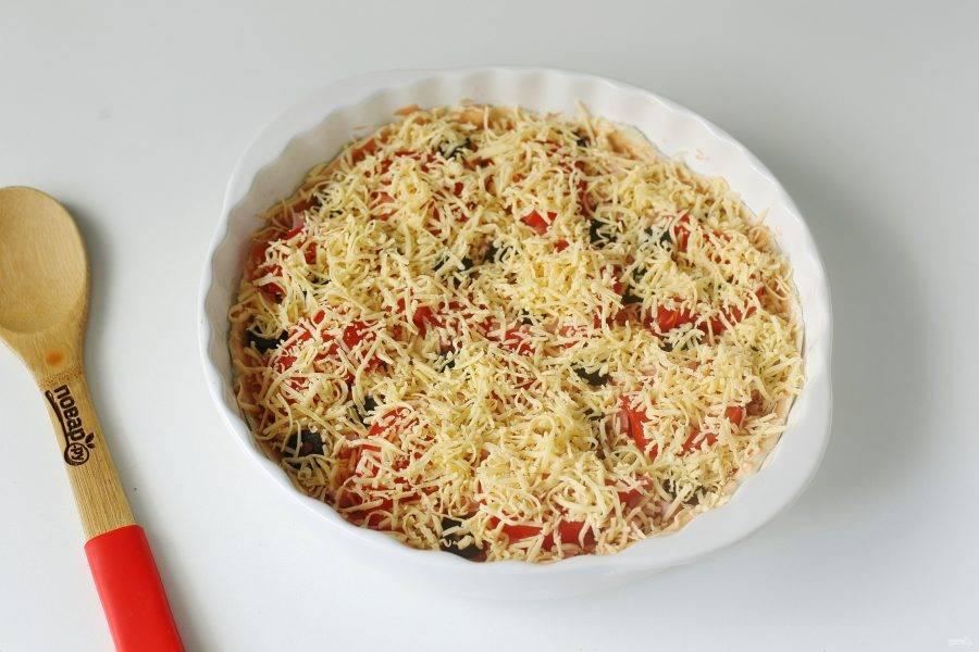 Посыпьте начинку тертым сыром и запекайте пиццу в духовке при температуре 220 градусов около 10-15 минут.