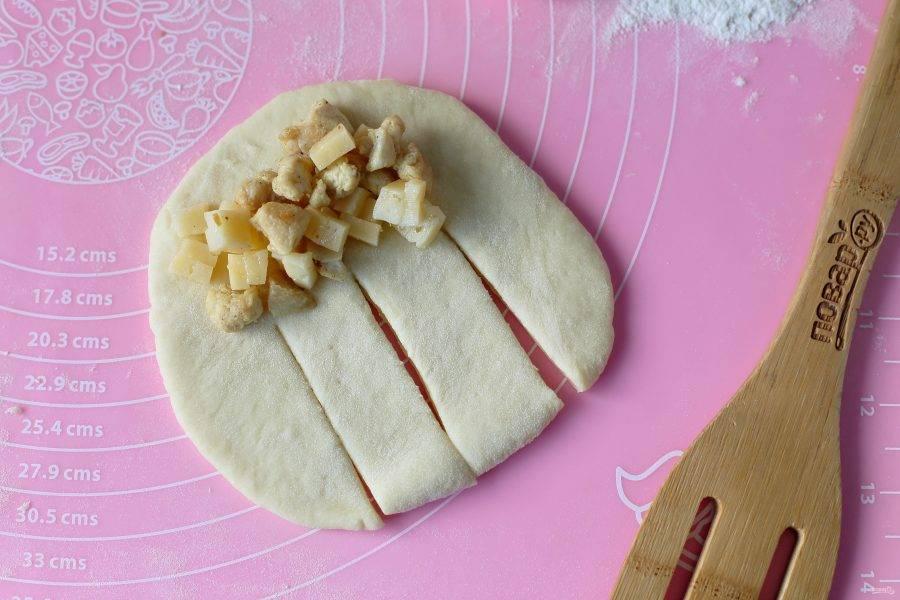 Затем раскатайте каждую заготовку в форме овала и ближе к одному краю выложите начинку. Со второй стороны нарежьте тесто на 4 полоски как на фото.