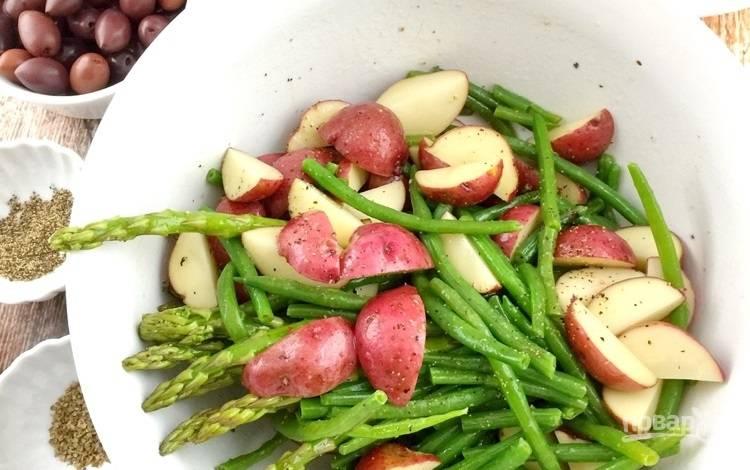 1.Отварите яйца и очистите их от скорлупы. Вымойте картофель в кожуре и нарежьте его дольками. Вымойте остальные овощи, слейте воду с консервированных оливок.  В большую миску выложите спаржу, зеленую фасоль и картофель, перемешайте.