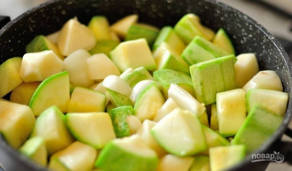 В сотейник с толстым дном или казанок влейте растительное масло и разогрейте его на плите. Кабачки вымойте и порежьте на крупные куски. Картофель, лук и чеснок почистите, промойте под водой и также нарежьте кубиками. Выложите овощи в сотейник и слегка обжарьте.