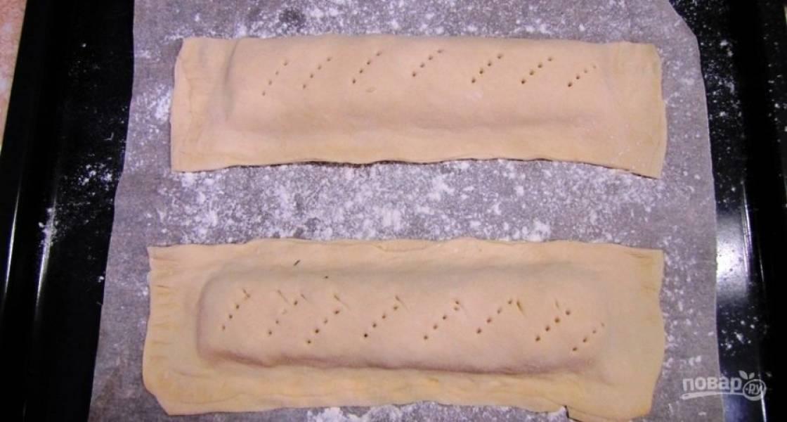 Тесто разрежьте. Выложите изделия на противень с пекарской бумагой, присыпанной мукой. Желток взбейте с водой. Смажьте тесто приготовленной смесью.