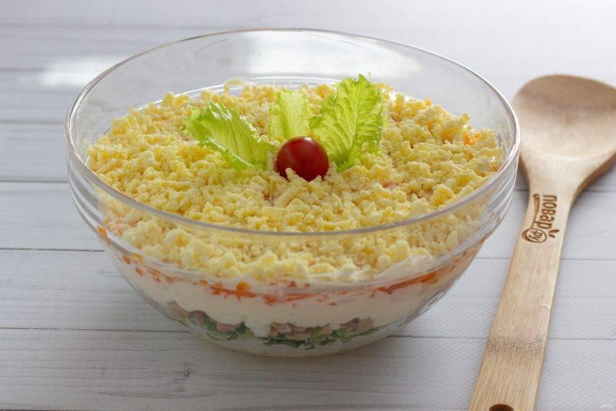 На мелкой терке натрите желтки и выложите последним слоем. Украсьте салат по своему вкусу и дайте немного пропитаться.