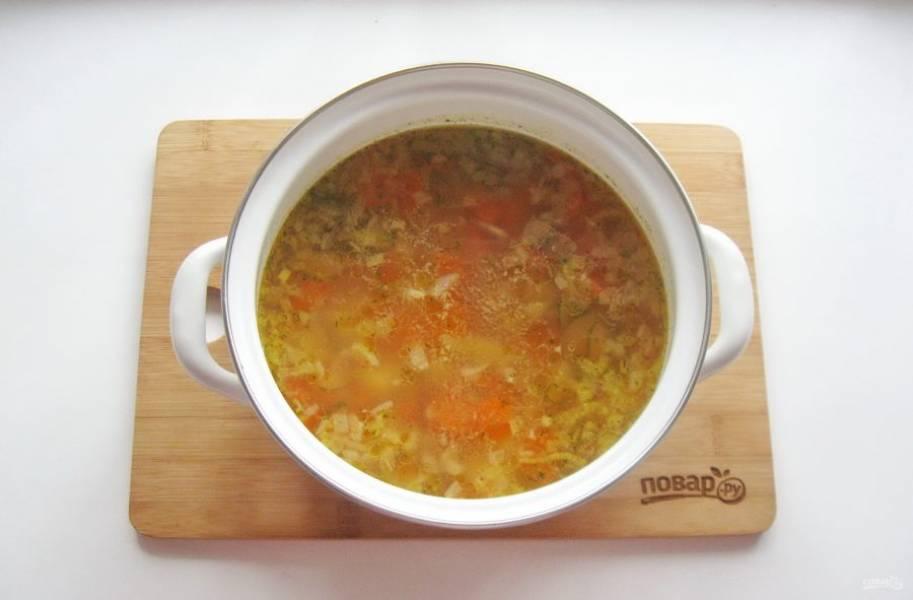 Когда овощи и рис будут готовы, добавьте в кастрюлю соленый огурец и помидоры. Посолите и поперчите по вкусу. Варите суп еще 10 минут и выключайте.