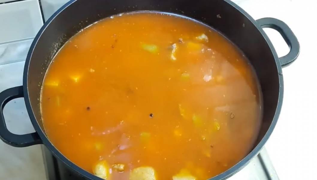4. Далее добавьте немного кипящей воды и дайте потушится в течении 10 минут. Добавьте картофель, перемешайте и добавьте необходимое количество жидкости. Проварите суп 10 минут, после чего добавьте в суп помидоры, чеснок и острый перец.