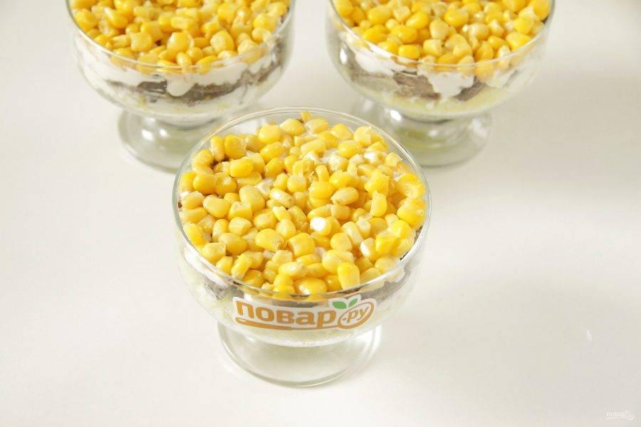 Сверху положите консервированную кукурузу.