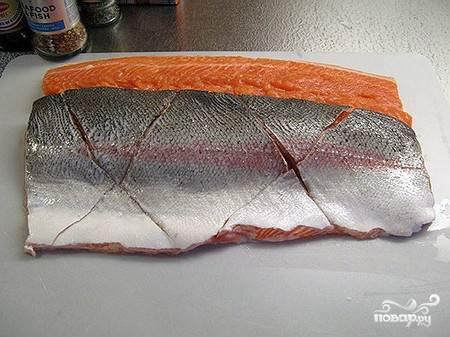 Чистим и разделываем рыбу. Удаляем все косточки, разрезав вдоль тушку. Делаем надрезы на одной стороне.