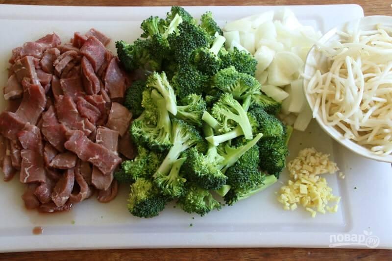 1.Вымойте мясо и нарежьте его тонкими плоскими полосками. Вымойте брокколи и разделите на соцветия. Очистите и нарежьте кубиками лук, измельчите чеснок и корень имбиря.