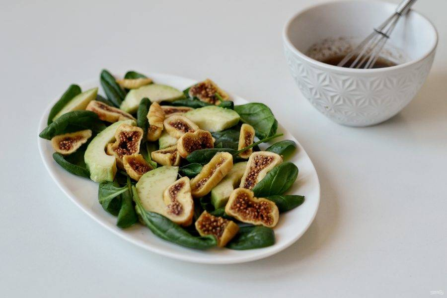 На дно блюда выложите зелень, ломтики инжира и авокадо. Полейте заправкой и сразу подавайте к столу.