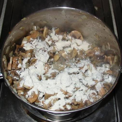 Посыпать грибы мукой, хорошо перемешать. Убедитесь, что все шампиньоны покрыты мучной массой.