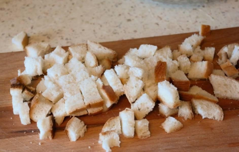Готовим сухарики. Берем четыре ломтика батона и нарезаем мелкими кубиками. Духовку разогреваем до 180 градусов. Выкладываем хлеб на противень, сбрызгиваем слегка оливковым маслом, перемешиваем и запекаем 10 минут.
