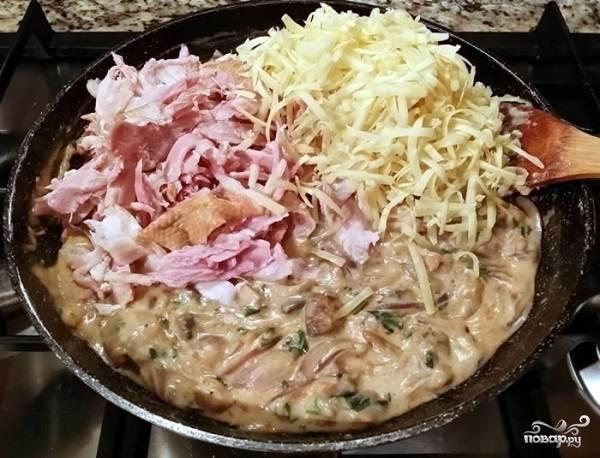 7. На сковороду добавьте тертый сыр и измельченную копченую курицу. Аккуратно все перемешайте и дайте сыру расплавиться. После этого можно снимать с огня.