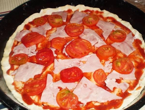 7. Разложить по всей поверхности помидоры и ломтики ветчины. Также пицца по-быстрому с ветчиной в домашних условиях может быть с грибочками, сладким перцем и другими ингредиентами, которые есть в холодильнике.