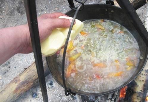 Также кладем очищенный картофель целиком. Если слишком крупный - режем пополам.