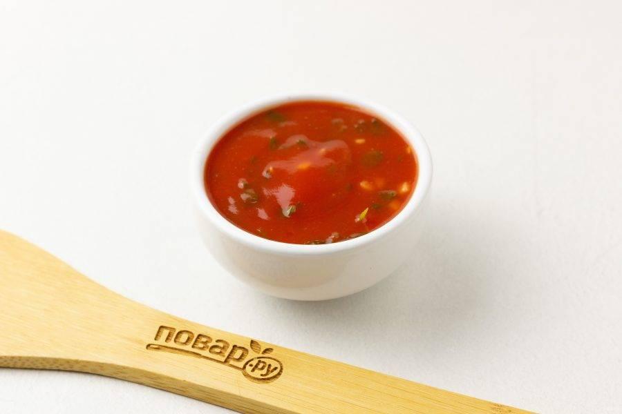 Приготовим соус. Томаты очистите от пленки, разомните и уварите вместе с соком 4-5 минут на сковороде. Затем добавьте рубленый чеснок, зелень, потушите  ещё 1-2 минуты и выключите плиту. Накройте соус крышкой, чтобы не остыл.