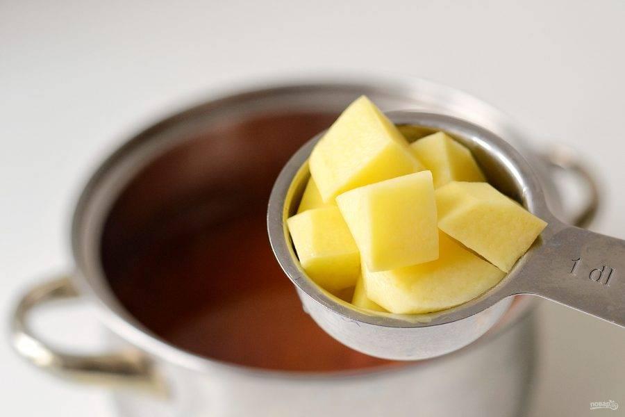 Добавьте картофель порезанный кубиками, варите суп еще 20 минут.