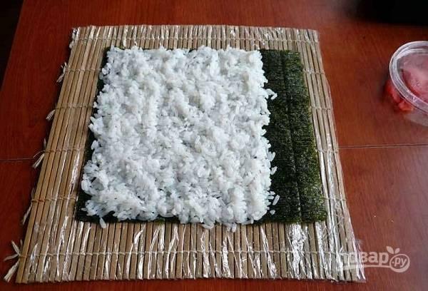 2. Выложите рис, чуть отступив от края, и плотно прижмите его влажными руками.