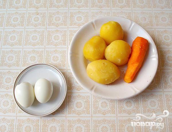 2.Отвариваем в кожуре морковь и картофель, остуживаем и очищаем. Очищаем луковицу и мелко ее нарезаем.  В растворе воды с уксусом, или в соке лимона ее замаринуем.